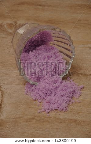 A bowl of purple bath salt on a wooden background