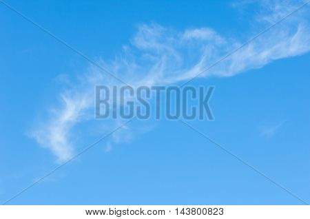 clouds in the blue sky. a visible mass of condensed water vapor floating in the atmosphere, typically high above the ground.