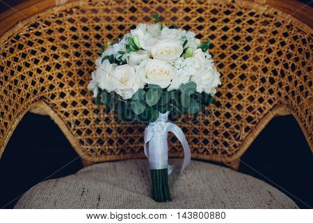Classic bridal bouquet of white flowers lying on a chair