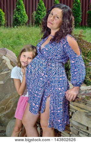 Pregnant woman joyfully embraces with her daughter