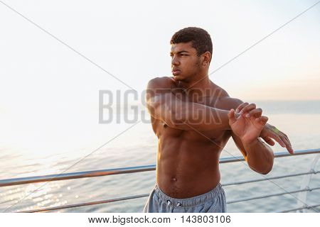 Athletic african american young sportsman standing and stretching arms on pier