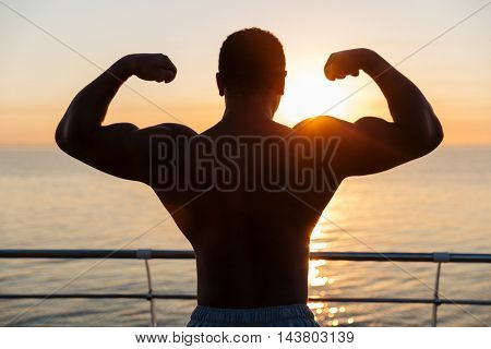 Silhouette of muscular young showing biceps outdoors at sunnrise