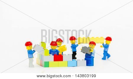 Orvieto, Italy - January 16th 2015: group of workman Lego mini figure build a wall. Lego is a popular line of construction toys manufactured by the Lego Group