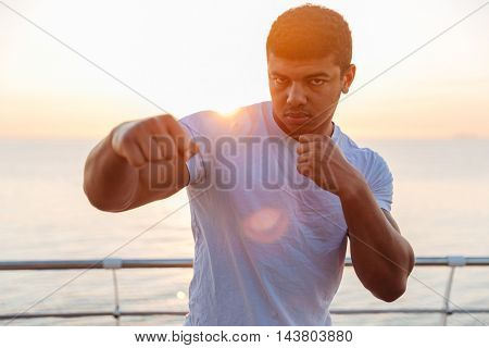 Handsome african american young man boxer practicing martial arts on sunrise