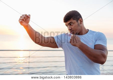 Concentrated african american young man boxer working out outdoors on sunrise