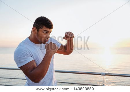 Concentrated african american young man boxer practicing shadow boxing outdoors in the morning