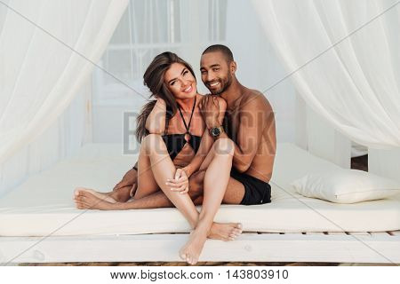 Portrait of beautiful young couple sitting on white bed together