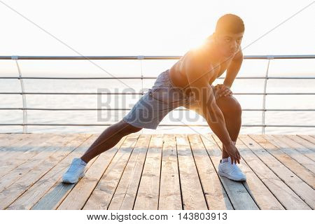 Handsome shirtless african american young man exercising and stretching legs