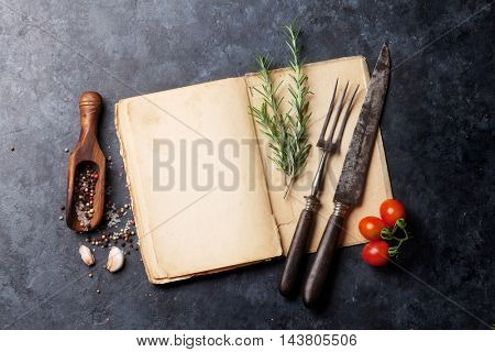 Blank cookbook for your text, herbs and spices. Top view over stone table with copy space