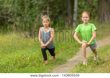 Two little girls warming up outdoors.
