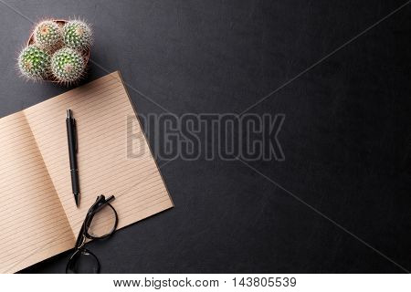 Office desk with notepad and glasses over leather texture. Top view with copy space