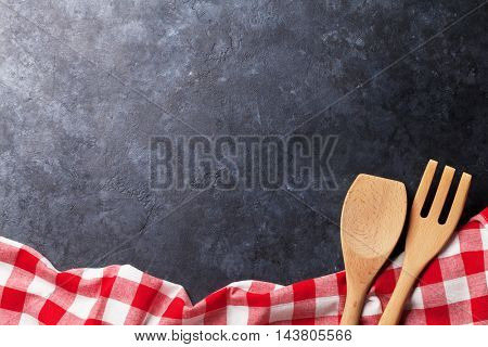 Towel and utensils over stone kitchen cooking table. Top view with copy space