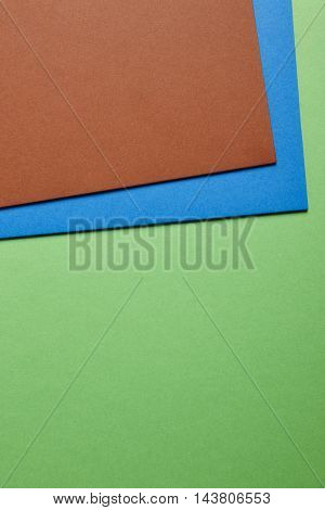 Colored cardboards background in blue green brown tone. Copy space. Vertical