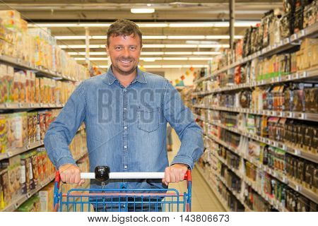 Smiling man driving shopping cart while grocery shopping in supermarket