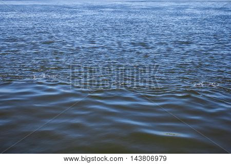 Wavy water surface of river with ripples, abstract background