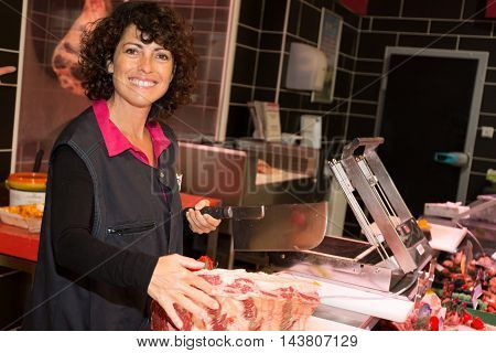 Saleswoman Cutting Sliced Meat At The Supermarket.