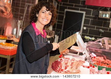 Smiling Saleswoman Cutting Sliced Meat At The Supermarket.