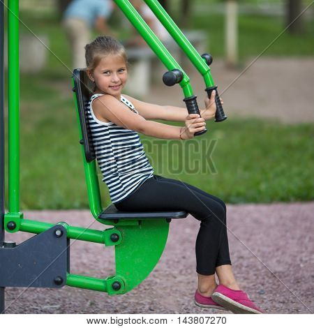 Funny little girl is engaged in sports equipment outdoor.