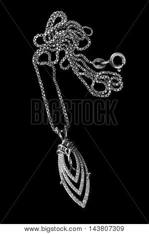 Diamond elegant pendant on a chain isolated over black