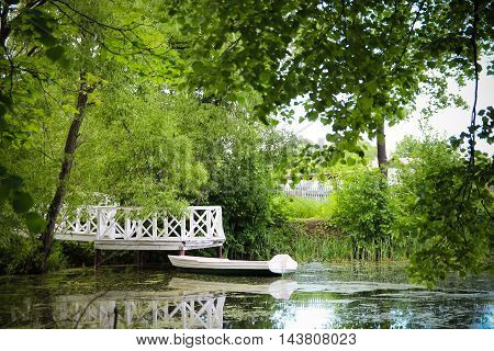 Old boat in the trees at the pier. Green trees overhang and create shade and comfort