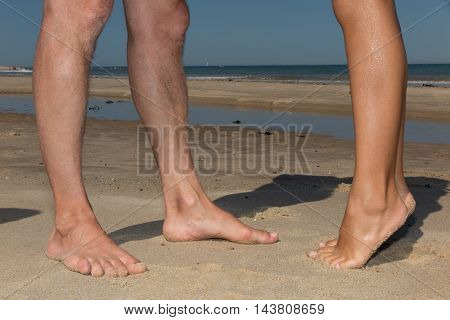Feet Of Couple Kissing On The Beach