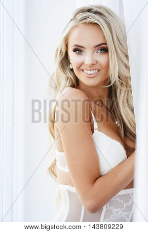 Portrait of attractive blond smiling woman in white