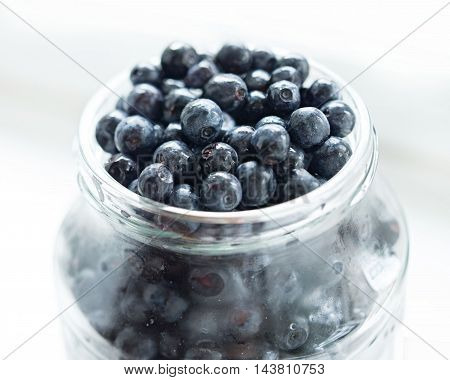 Blueberries in glass jar on a white background