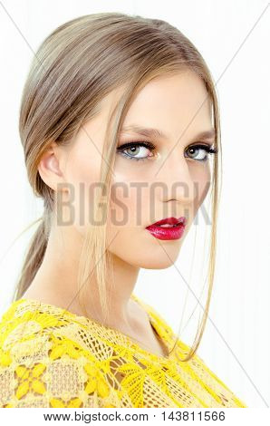 Fashion style portrait of a beautiful girl in interior. Beauty Fashion Model Woman face. Portrait with perfect skin. Red Lips.