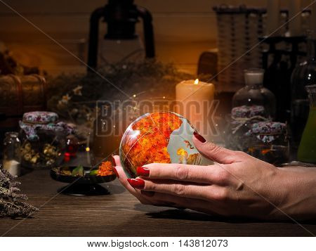 Female hand holding a magical fiery sphere. The golden glow. Flasks retort for alchemy. Concept - occult esotericism spiritualism calling the spirits and ghosts underworld