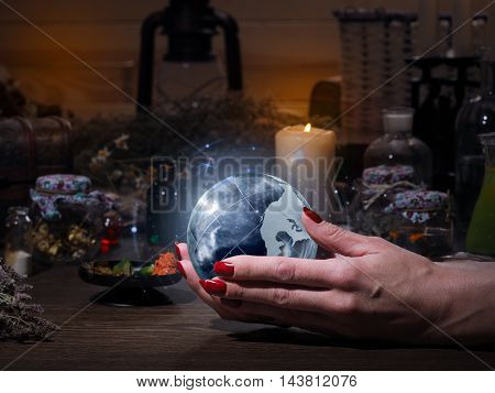 Women's hands holding the magic sphere with the stars. The blue glow. Flasks retort for alchemy. Concept - the world of astrology stars prediction occult spirituality spiritualism