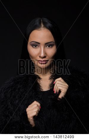 Portrait of brunette model woman posing for photographer in studio. Beautiful lady with black hair wearing expensive fur isolated on black background.