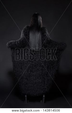 Picture of brunette model woman showing her back while posing for photographer in studio. Beautiful lady wearing expensive fur coat.