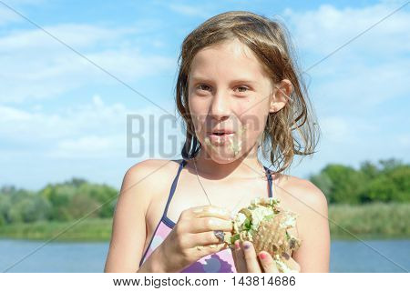 girl on the beach on the riverbank snack hot sandwiches