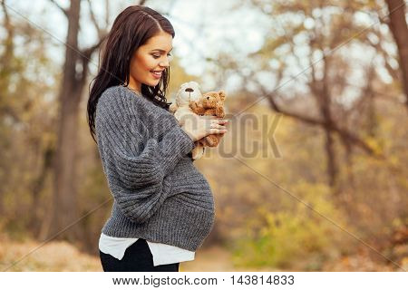 Pregnant woman in the park holding teddy bear and bunny toy