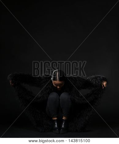 Brunette model woman posing in fur coat while promoting it for fashion or vogue magazine in studio. Beautiful woman looking down isolated on black background.