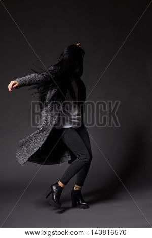 Brunette model woman dancing in studio while posing for photographer demonstrating designers' clothes isolated on grey background.