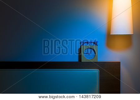 Bed headboard over head lamp alarm clock and reading glasses at night in contrasting cold blur and warm orange color tones in simple and minimalist design with room for copy space