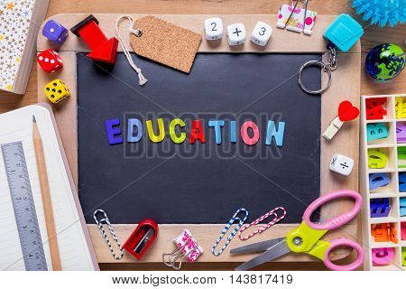 Small blackboard surrounded with various stationary with Education word in the middle on wood background