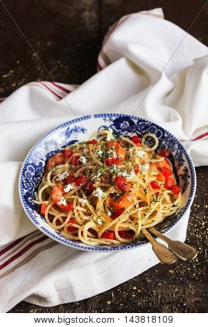 Cooked spaghetti pasta dish with roasted shrimps, chopped fresh tomatoes, red sweet pepper and salted greek feta cheese with chopped fresh dill in a bowl, selective focus