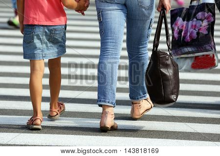 woman with a child going through the crosswalk