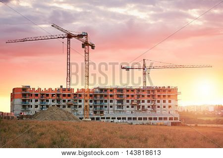 Construction site with cranes at the amazing sunset. Construction of the new residential building. Prague Czech Republic.