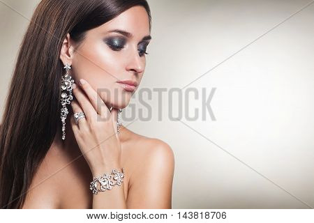 Portrait of beautiful sexy young brunette woman with luxury jewelry: earings, bracelet, rings