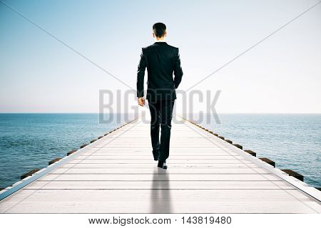 Businessman walking on wooden pier. Blue sea and sky background with abstract sunlight. Success concept