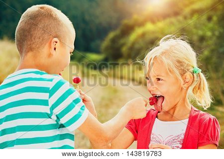 Children enjoying sunny day in holiday. Cheerful little boy and little girl tasting lollipops.