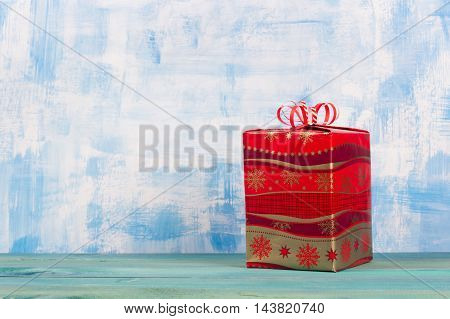 Christmas present box over blue wooden background, above view