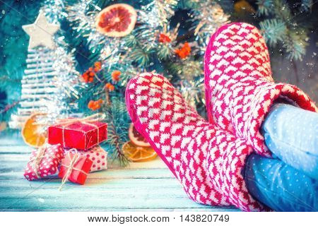 Woman Relaxes Her Feet In Woollen Socks.winter And Christmas Holidays Concept.