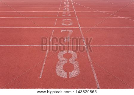 Starting lane with numbers on Red running track for athletics and competition