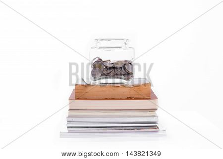Book pen with penny jar filled with coins money on white background. education financing concept