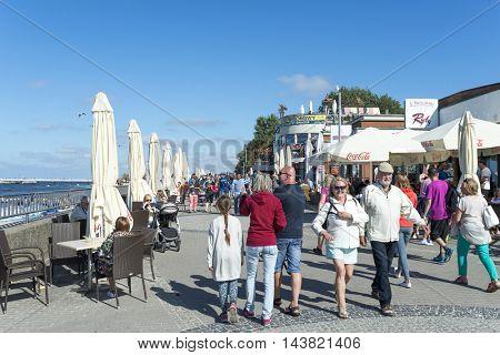 KOLOBRZEG - AUGUST 15: Promenade along the beach with the walking vacationing people on 15 August 2016 in Kolobrzeg, Poland.