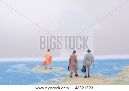 Miniature business people travel going home on world map. business international travel concept